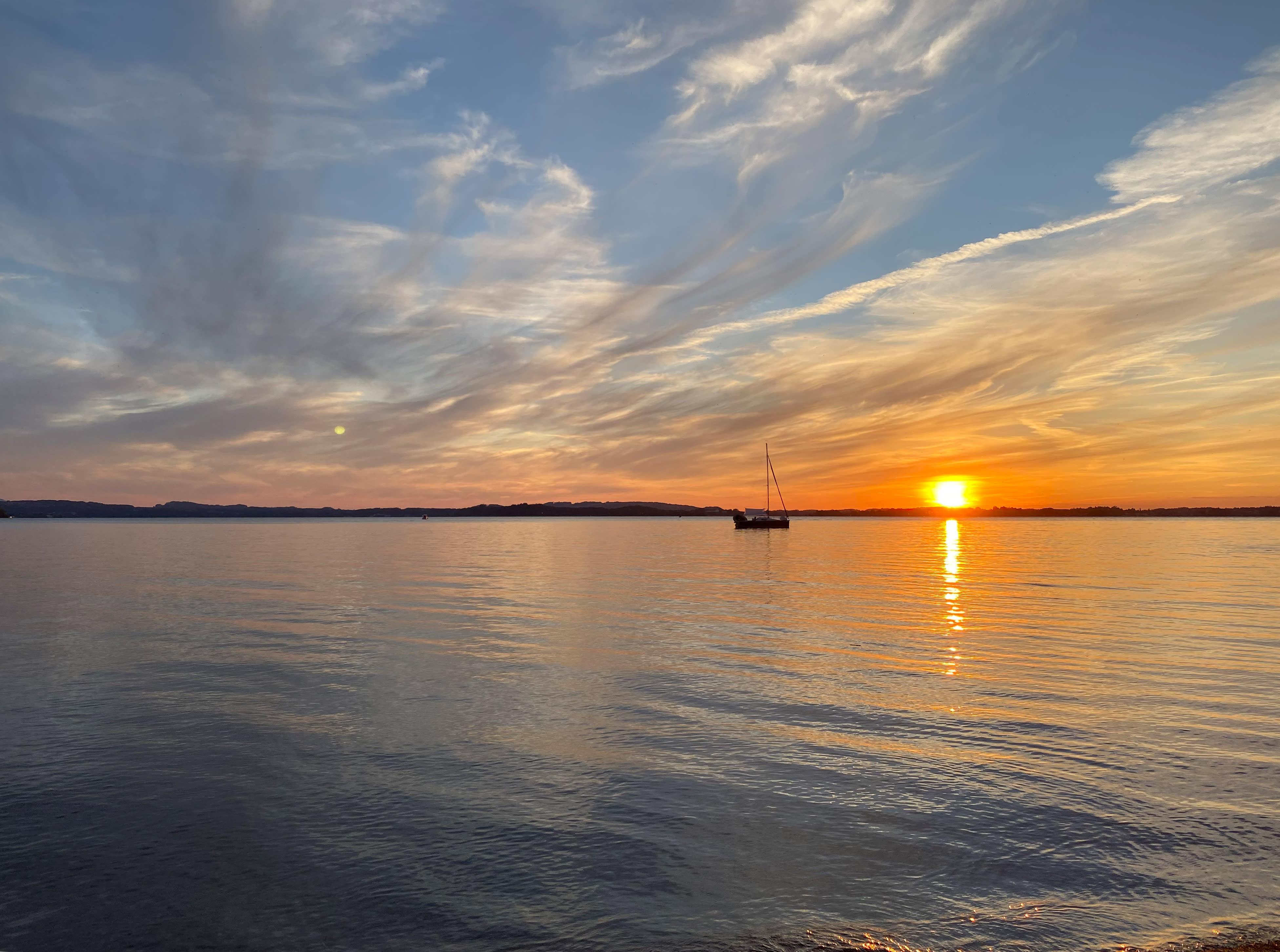 Boot treibt einsam bei Sonnenuntergang auf Chiemsee