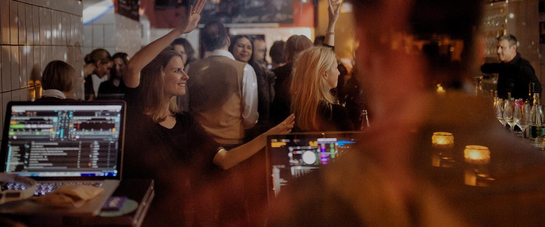 Blick durch Fenster auf DJ-Pult und tanzende Frau